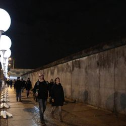 People walk between balloons of the art project 'Lichtgrenze 2014' (lit. 'lightborder 2014') and the remains of the former Berlin Wall at the wall memorial site Bernauer Strasse in Berlin, Germany, Friday, Nov. 7, 2014. The light installation featuring 8,000 luminous white balloons commemorates the division of Berlin where the 25th anniversary of the fall of the wall is marked with numerous events on the weekend.