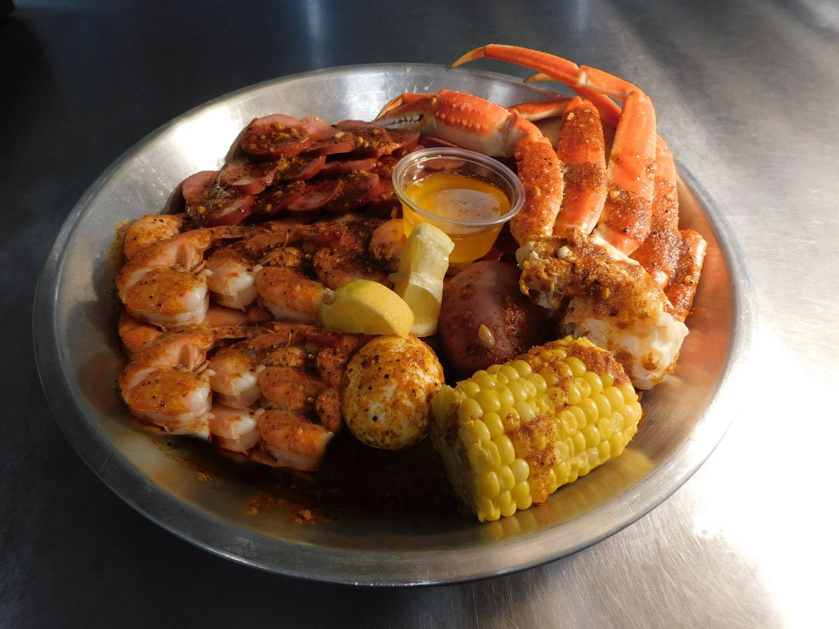 Shrimp, crab legs, and corn on a metal plate