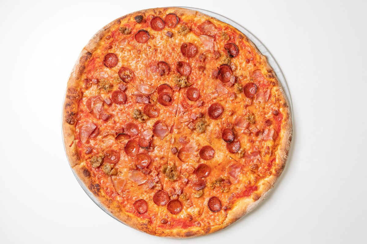 An overhead shot of a full pizza with pepperoni and sausage.