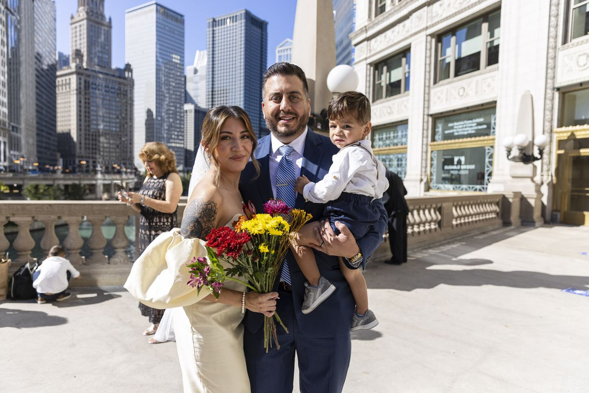 Perla and Edgar Bernal and their son pose for a photo near the Wrigley Building on N Michigan Ave during the Meet Me on The Mile Sunday Spectacle Sunday, Sept. 26, 2021. 50 couples were | Anthony Vazquez/Sun-Times