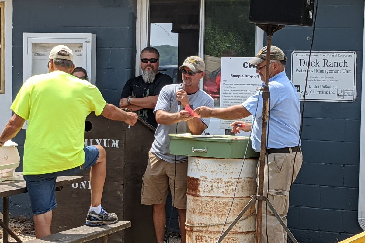 Retired site superintendent Tony Colvin (microphone) announces a successful person at the waterfowl blind draw at Marshall State Fish and Wildlife Area. Credit: Dale Bowman