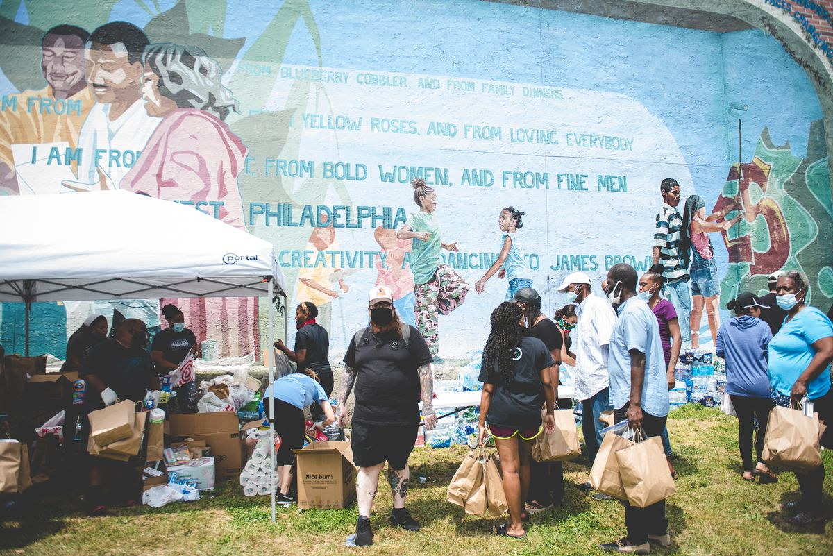 groups of people holding brown bags in front of mural