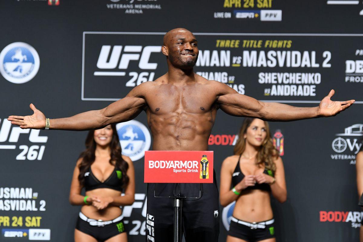 2021年4月23日,在佛罗里达州杰克逊维尔的VyStar老兵纪念体育场,UFC中量级冠军、尼日利亚选手卡马鲁·乌斯曼在UFC 261称重仪式上的体重秤上摆姿势。