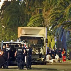 Police stand by as medical personnel attend a person on the ground, right, in the early hours of Friday, July 14, 2016, on the Promenade des Anglais in Nice, southern France, next to the lorry that had been driven into crowds of revelers late Thursday. France has been stunned again as a large white truck killed many people after it mowed through a crowd of revelers gathered for a Bastille Day fireworks display late Thursday evening, in the Riviera city of Nice.
