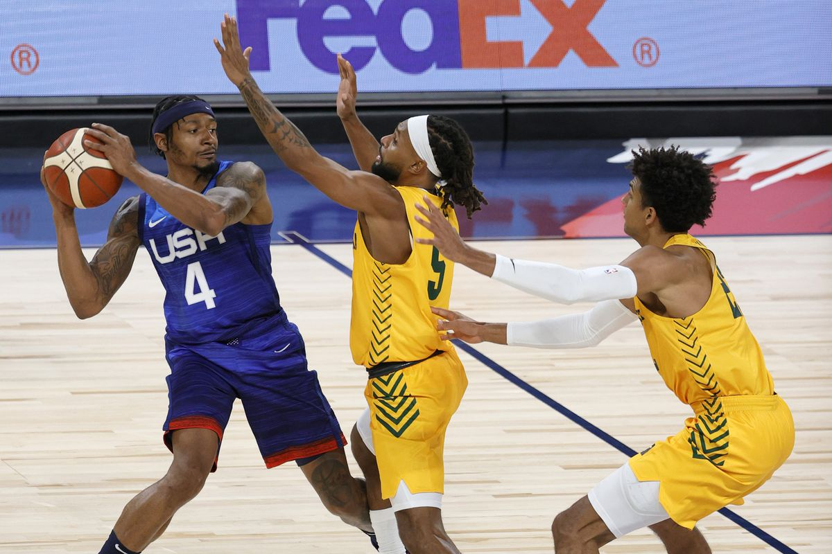 Bradley Beal of the United States is guarded by Patty Mills and Matisse Thybulle of the Australia Boomers during an exhibition game at Michelob Ultra Arena ahead of the Tokyo Olympic Games on July 12, 2021 in Las Vegas, Nevada. Australia defeated the United States 91-83.