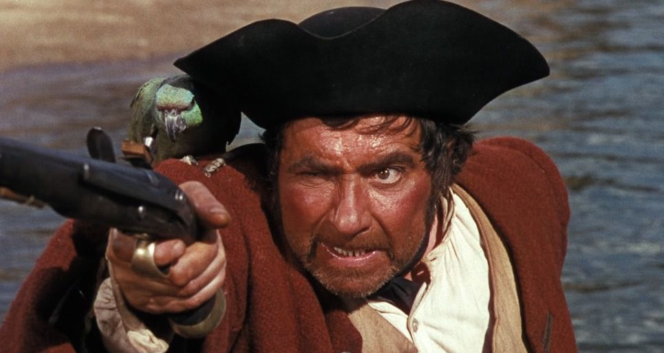 a pirate points his gun with his parrot on his shoulder yar this is treasure island