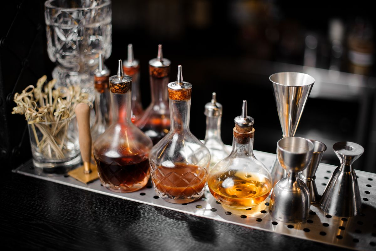 Various colorful tinctures and jiggers set up on a bar counter.