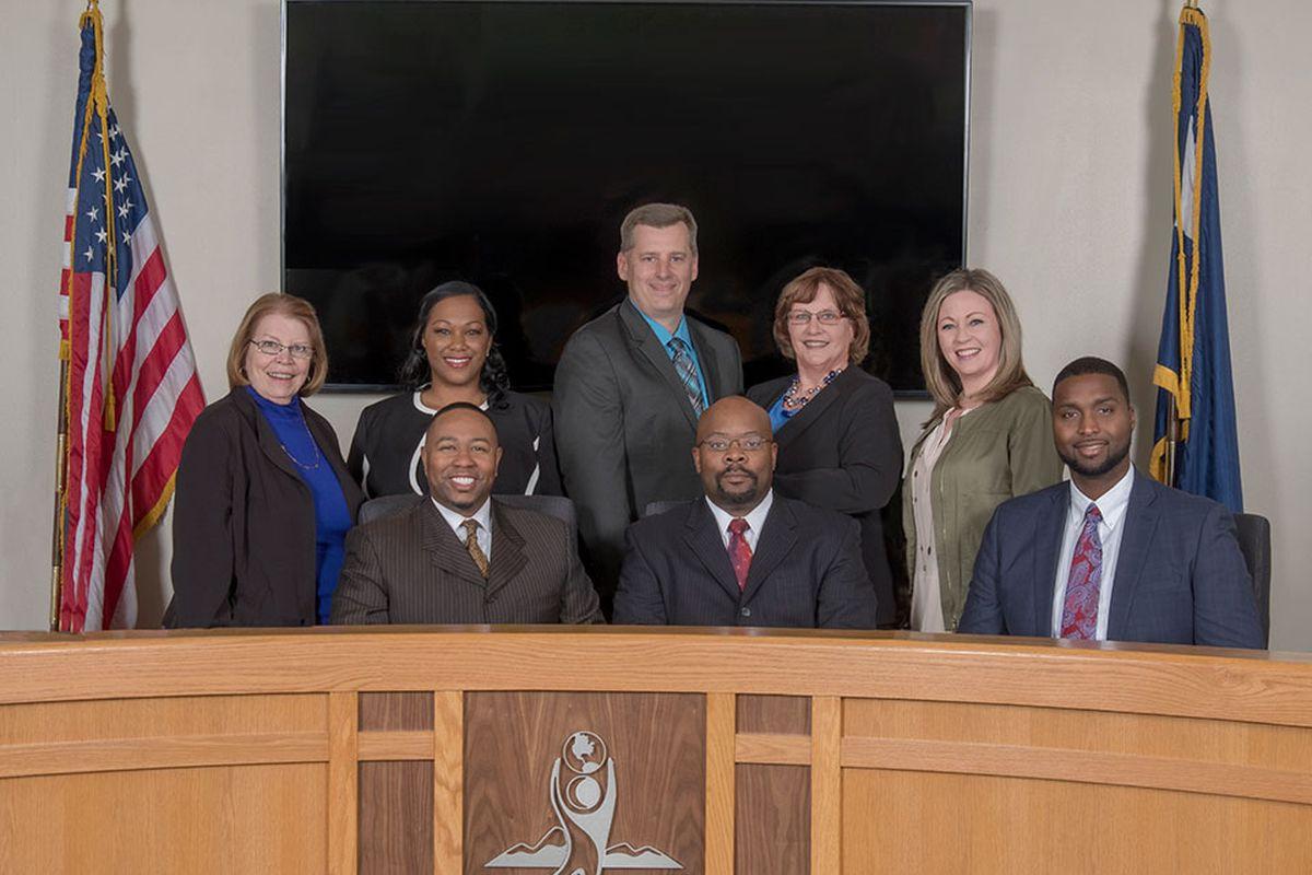 Aurora Public Schools board of directors and Superintendent Rico Munn, center.