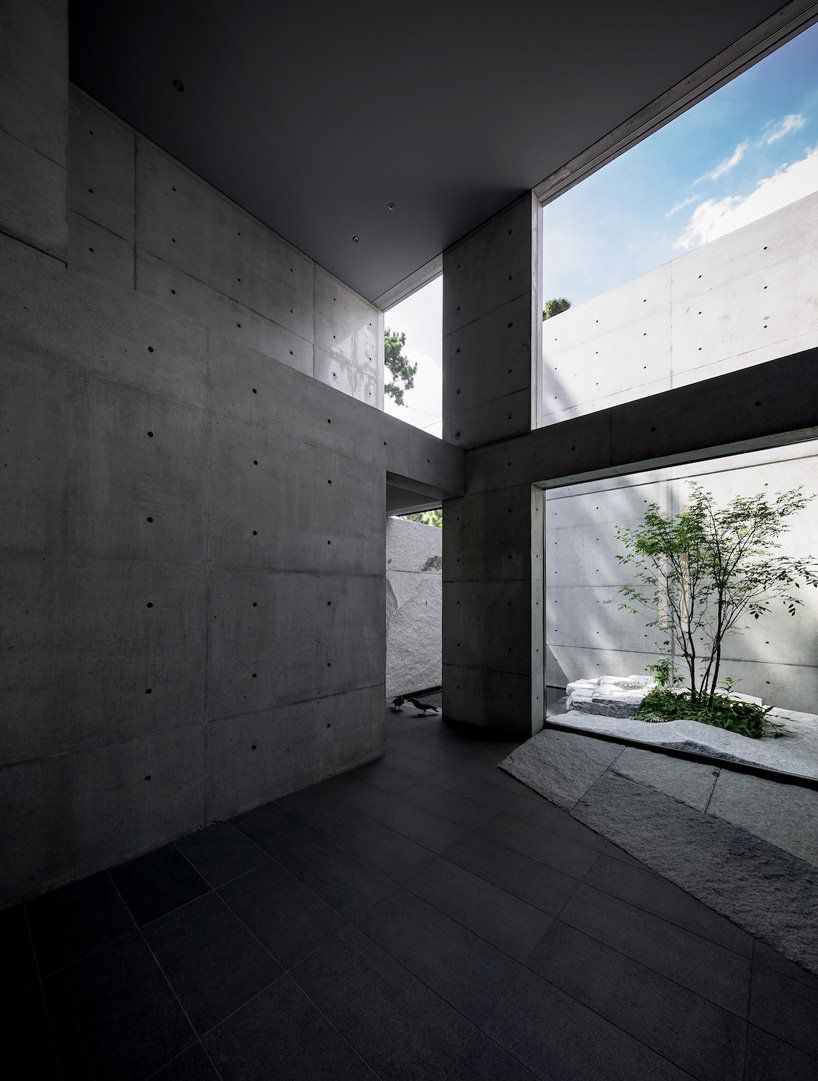All-concrete room with high ceilings and an opening to an outdoor zen garden.