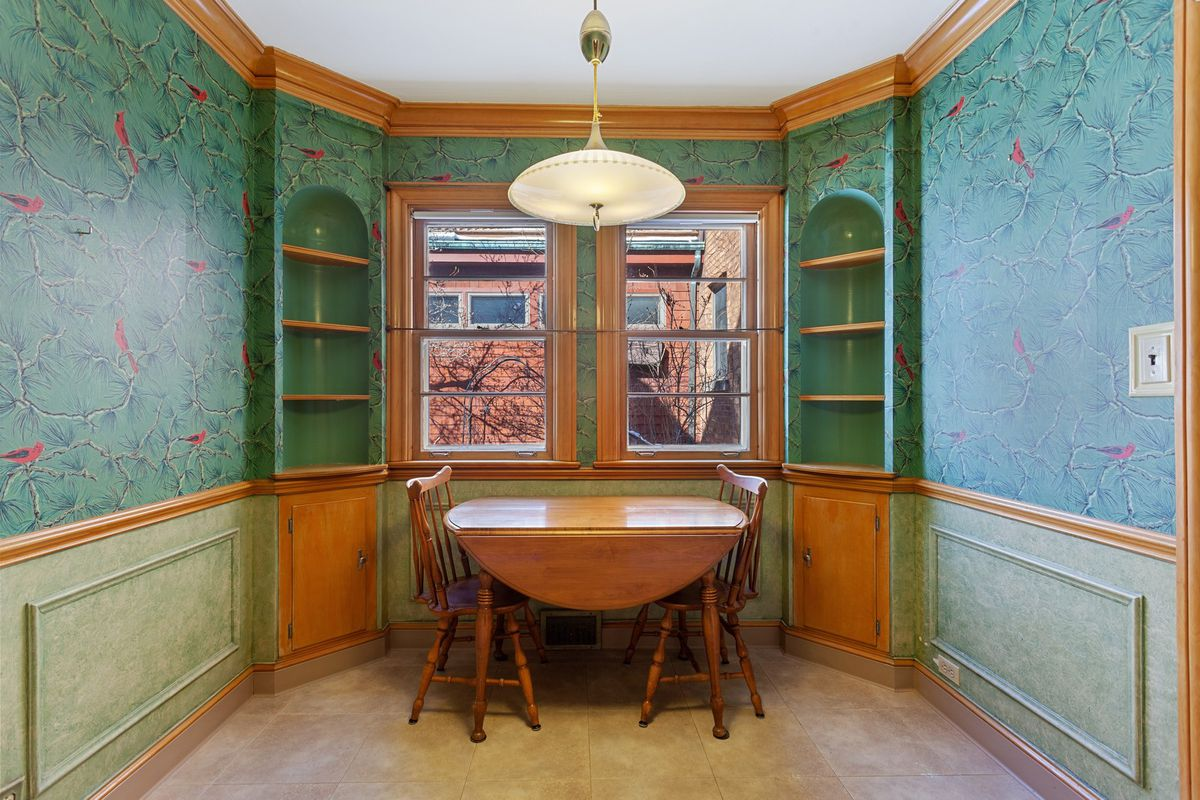 A breakfast nook with built-in shelves, a small wooden table, windows, and wallpaper with evergreen and robins.