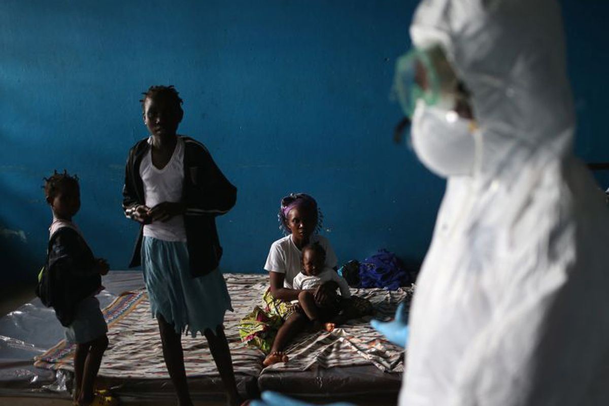A Liberian health worker speaks with families in a classroom now used as Ebola isolation ward on August 15, 2014, in Monrovia, Liberia.