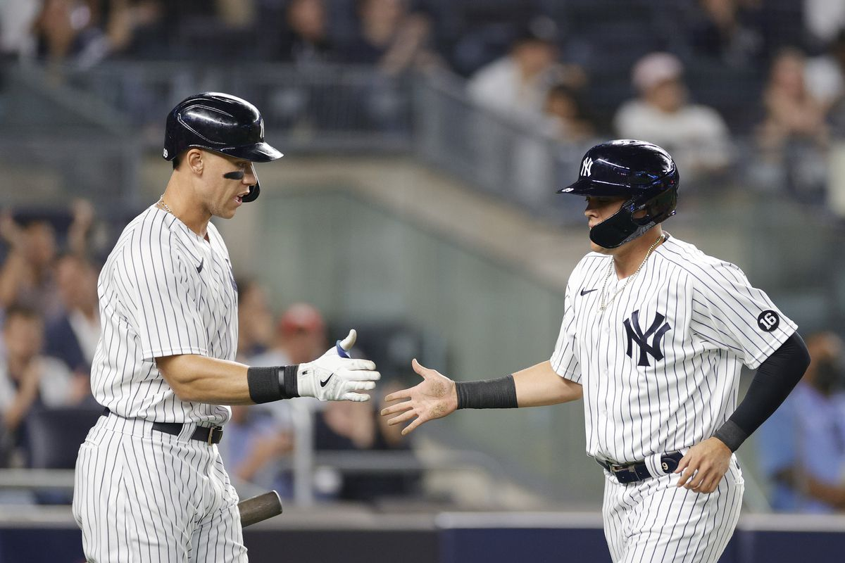 Gio Urshela #29 high-fives Aaron Judge #99 of the New York Yankees after scoring off of a single hit by Anthony Rizzo #48 (not pictured) during the fifth inning against the Texas Rangers at Yankee Stadium on September 21, 2021 in the Bronx borough of New York City.