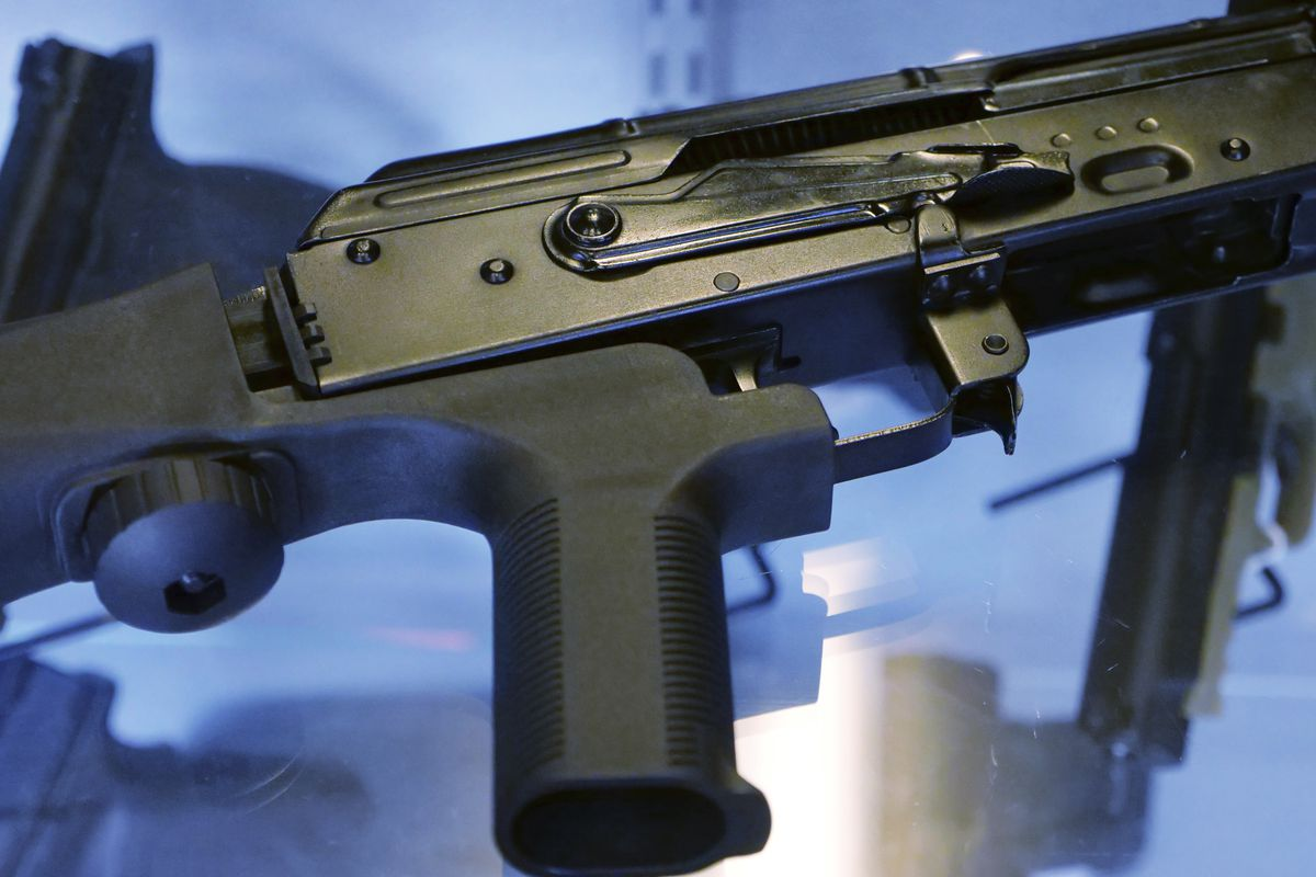"""FILE - In this Oct. 4, 2017 file photo, a device called a """"bump stock"""" is attached to a semi-automatic rifle at the Gun Vault store and shooting range in South Jordan, Utah."""