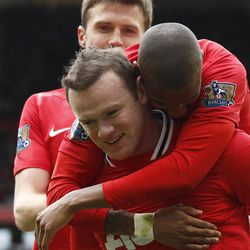 Manchester United's Wayne Rooney, center, celebrates with teammates after scoring a penalty against Aston Villa during their English Premier League soccer match at Old Trafford Stadium, Manchester, England, Sunday, April 15, 2012.