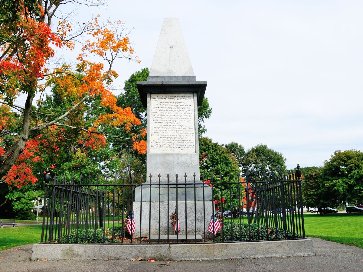 An obelisk-shaped war monument behind an iron fence.