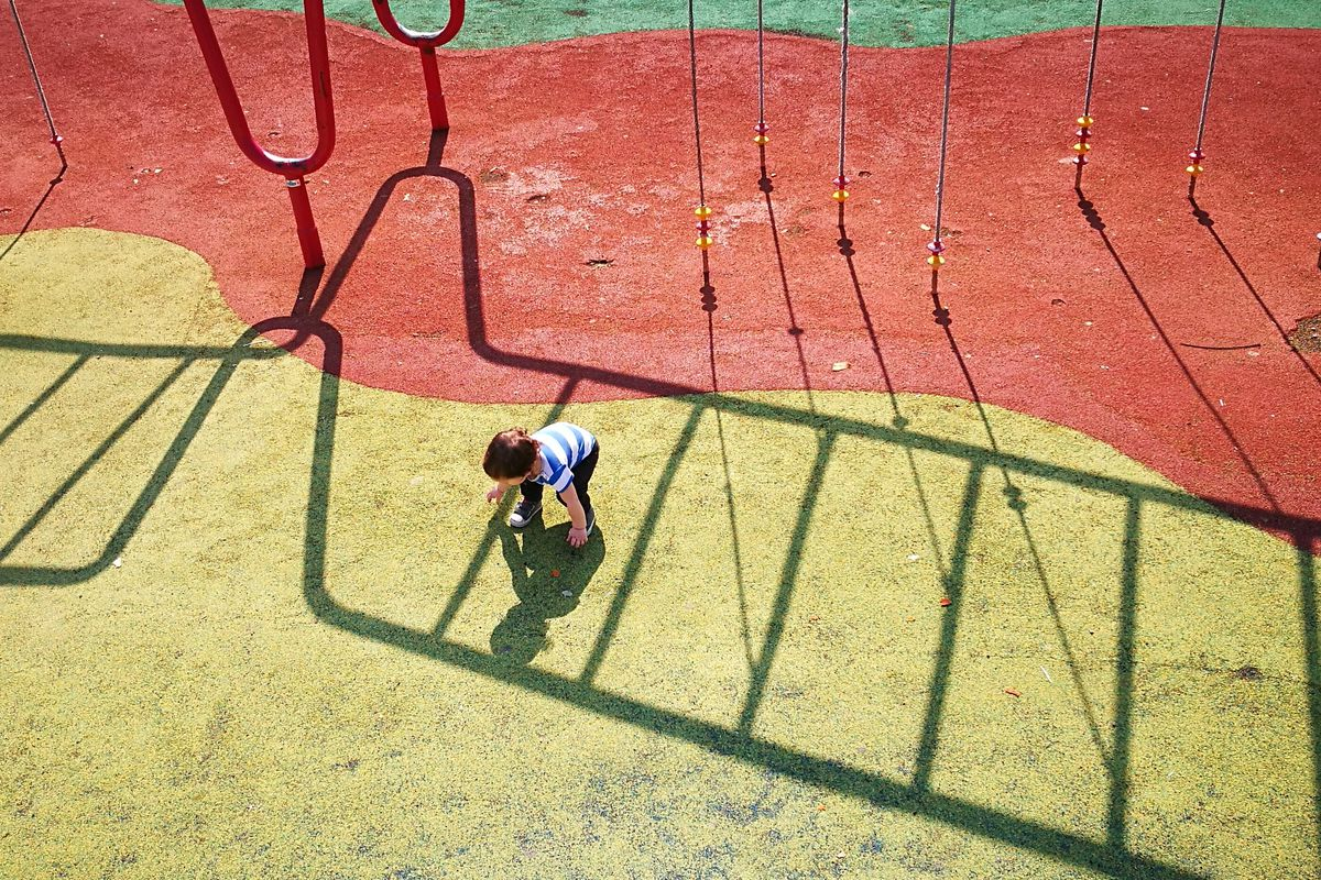A small boy leans down to touch his shadow on a red and yellow playground surface.