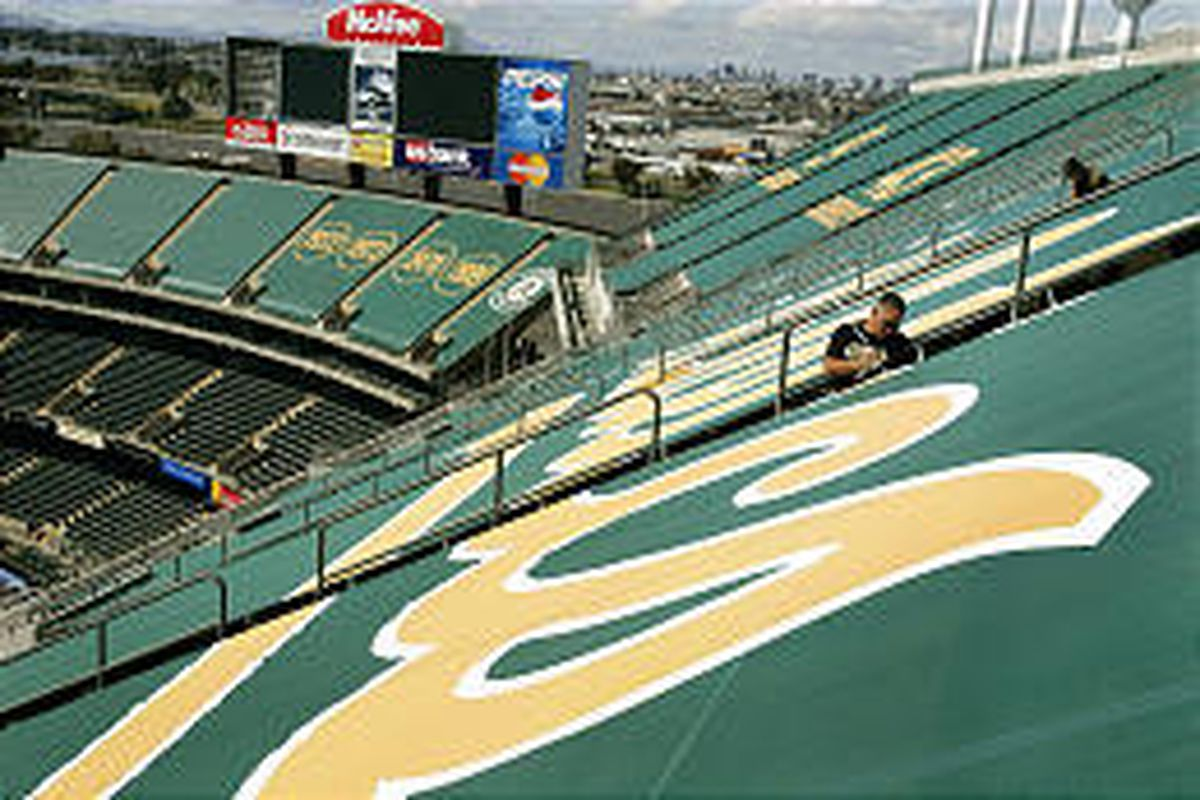 Mike Lawson affixes a green panel over upper deck seats at McAfee Coliseum in Oakland, Calif. Fusion Imaging of Kaysville created the vinyl mesh panels.