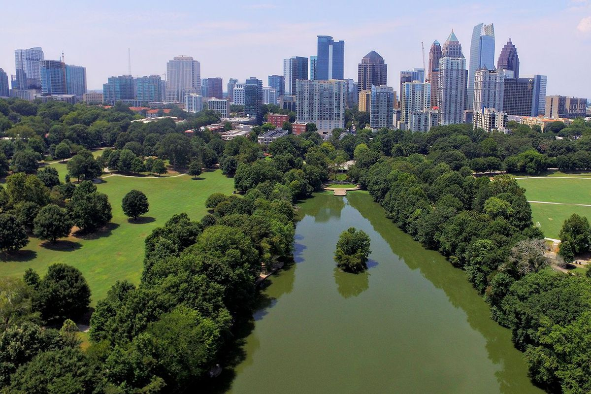 A drone image taken over a large green park with a lake just below, and a skyline just beyond.