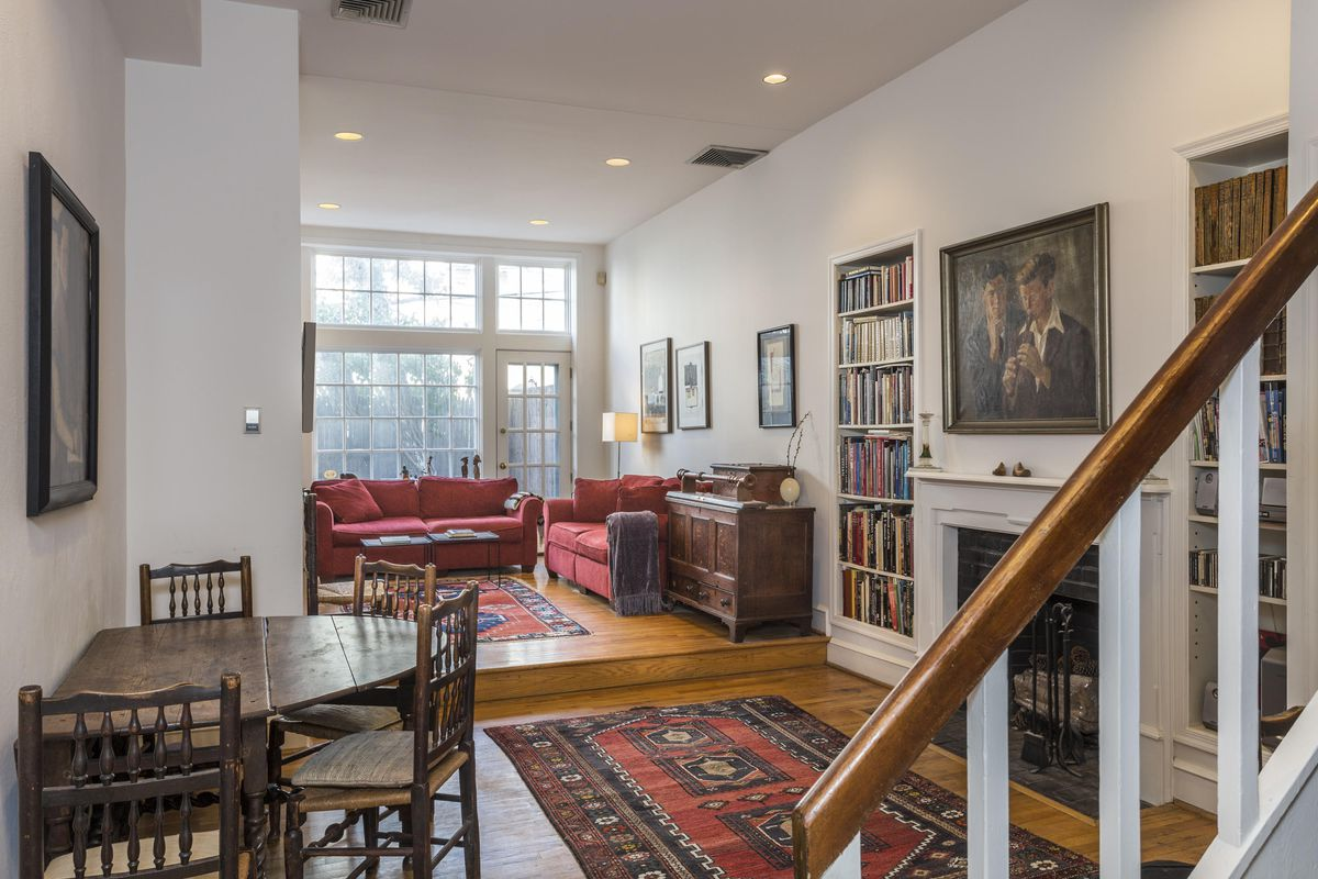 Looking into a living room with floor-to-ceiling windows, a fireplace sandwiched between built-ins, and hardwood floors.