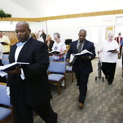 Rev. Jerrod Lowry leads Pastor Ron Williams at the Community of Grace Presbyterian Church in Sandy Sunday, Aug. 17, 2014.
