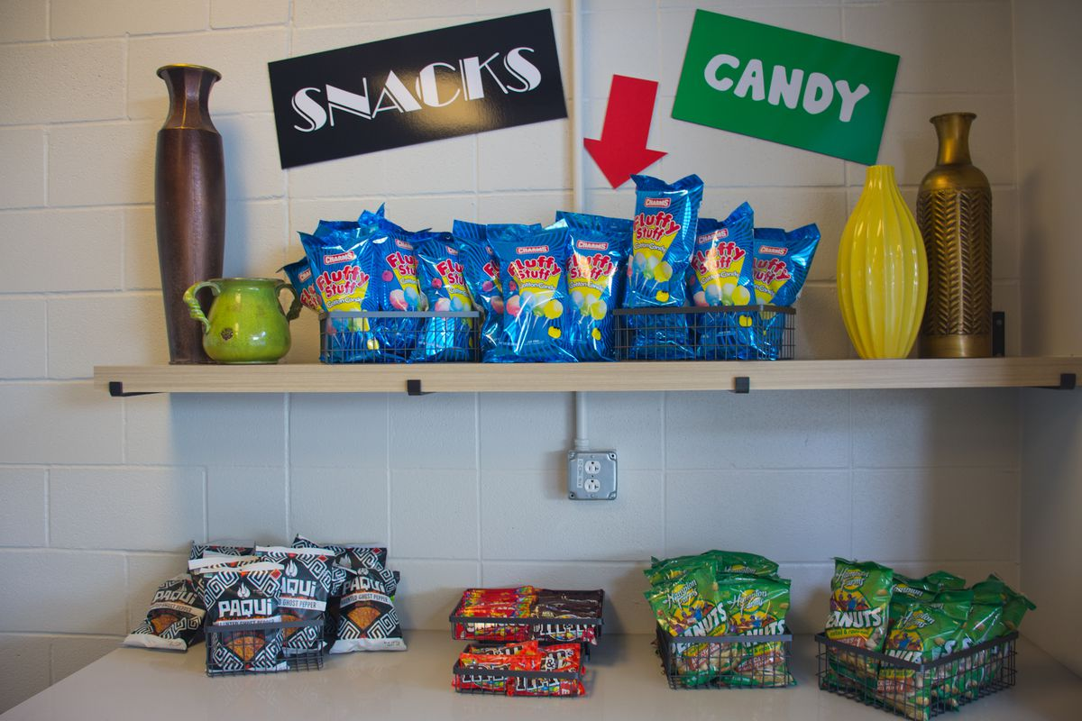 """A counter and a shelf with containers full of bagged snacks, underneath two ones, one that reads """"Snacks"""" and the other """"Candy"""""""