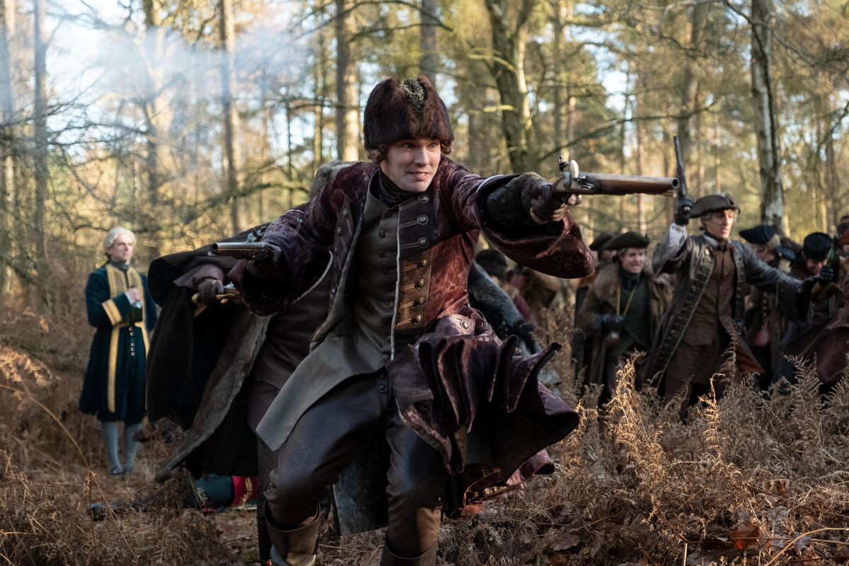 Nicholas Hoult, in an elaborate period hunting costume and furry hat, brandishes a flintlock pistol as he charges through the woods with a number of other men behind him.