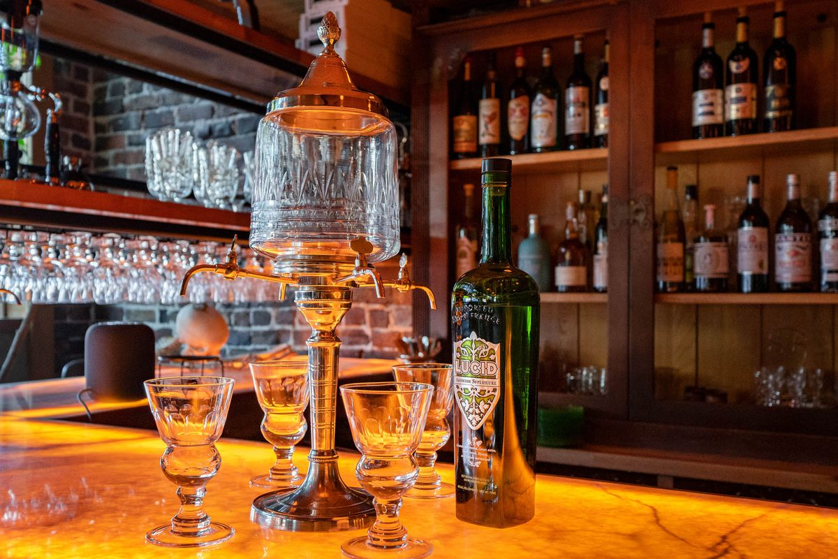 A glass absinthe fountain next to a green bottle of absinthe and four glasses on a honey-colored bar.
