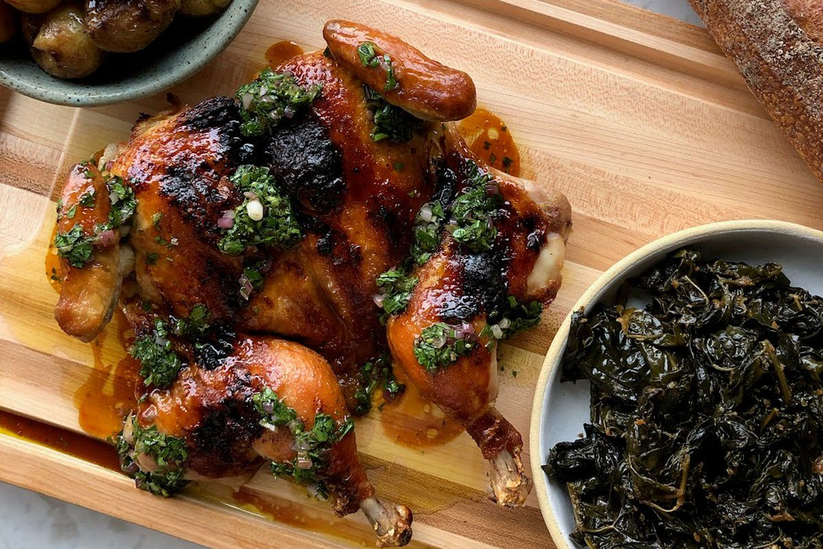 A splayed out roast chicken on a wooden cutting board, surrounded by a bowl of greens and a baguette.