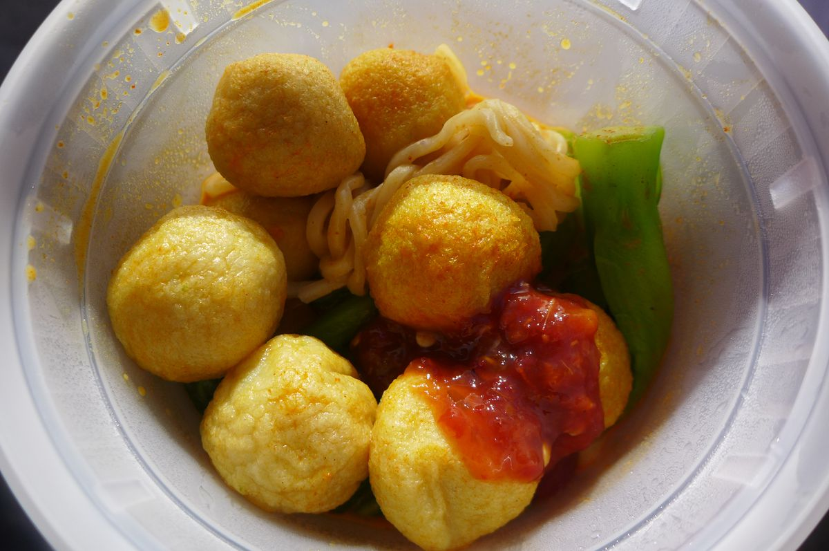 Round yellow balls in a deep plastic container with green vegetable and noodles flooded with sunlight.
