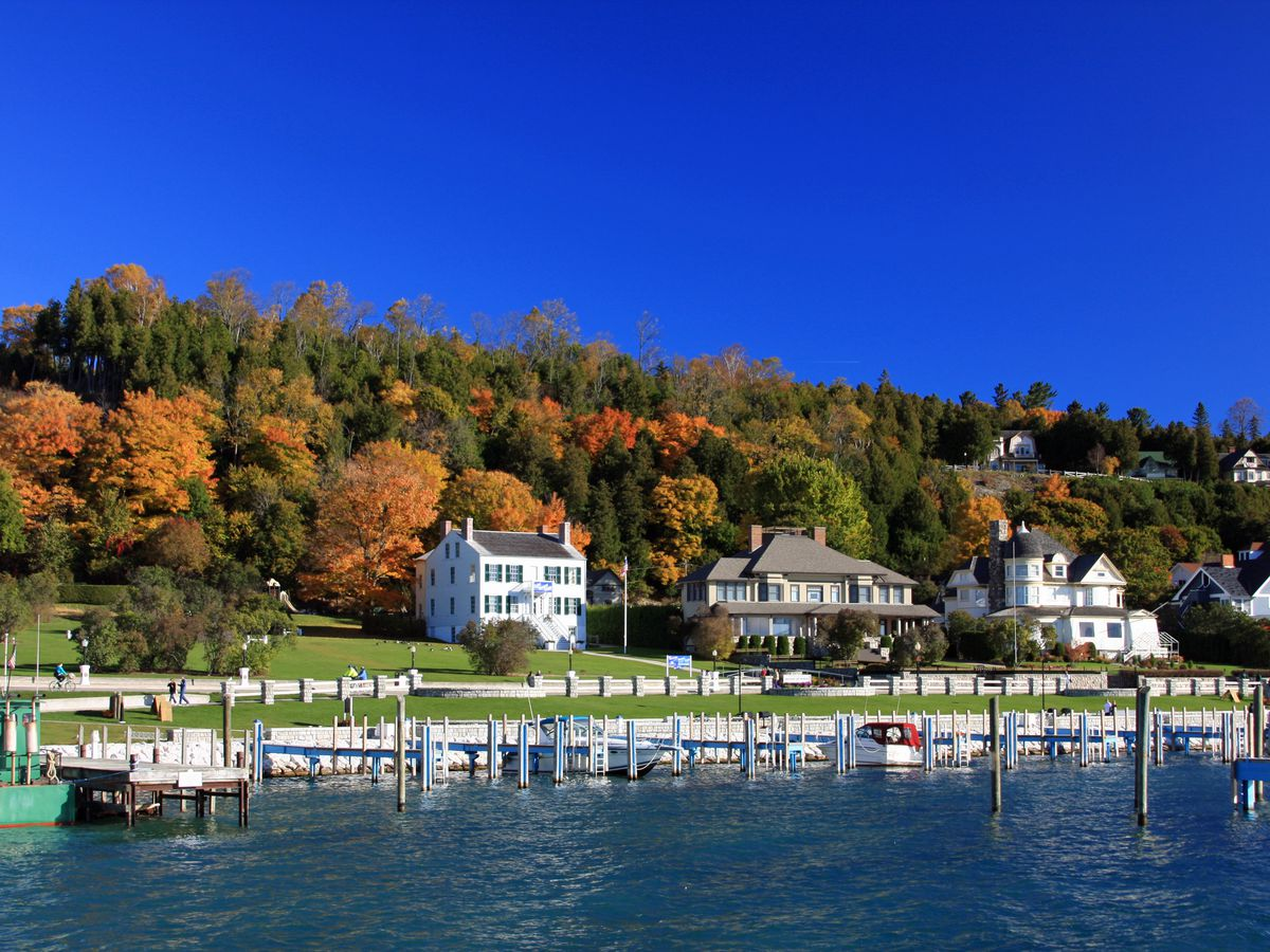 A waterfront with a pier and houses. In the background are trees with colorful autumn leaves.