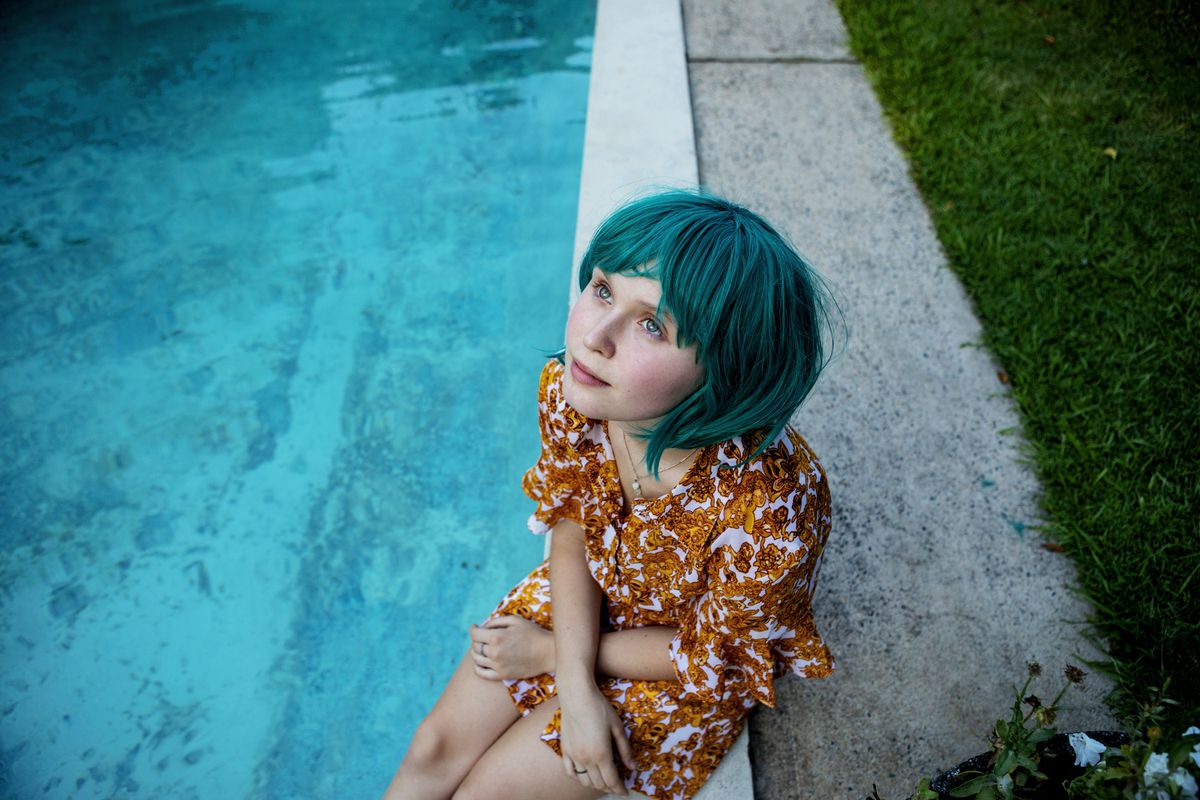 A girl in a blue wig sits with her feet in a pool.