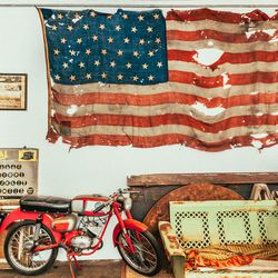 More evidence of hoarding, and what will eventually be a lounge but has a metal patio couch as a place holder. The motorcycle is a 1964 Benelli I just finished restoring, and the flag is an unofficial 42 star American flag from 1893. I am not terribly pat