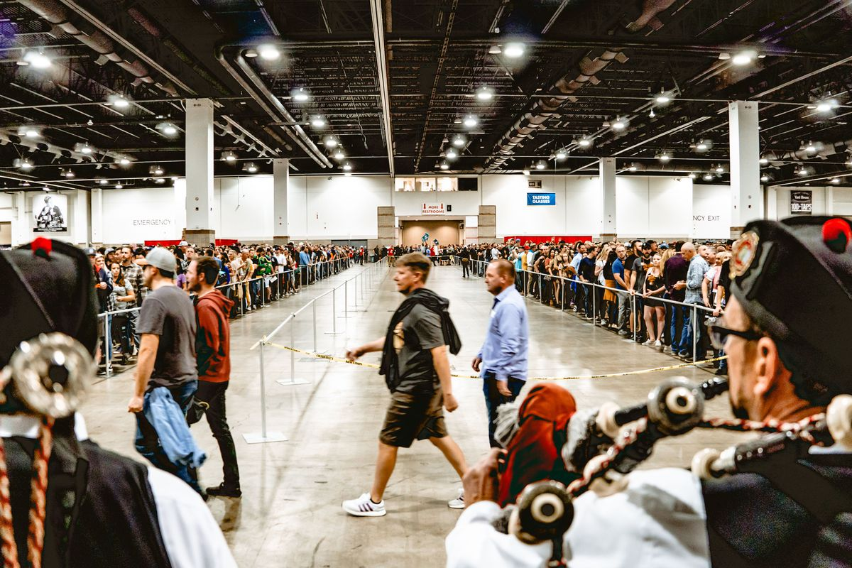 A photo of bagpipers seen from behind playing to crowds waiting to enter the Great American Beer Festival