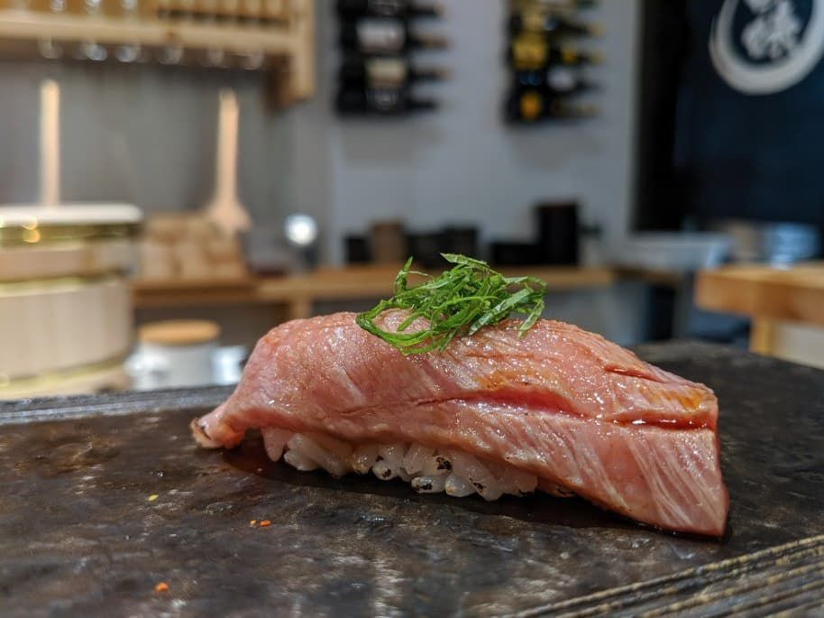 A rare, barely torched piece of A5 wagyu sits atop white rice at a sushi bar