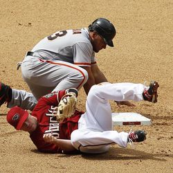 Arizona Diamondbacks' Aaron Hill, front, takes a tumble after falling over San Francisco Giants' Melky Cabrera, who dives back safely into second base during the sixth inning in an MLB baseball game Sunday, April 8, 2012, in Phoenix.