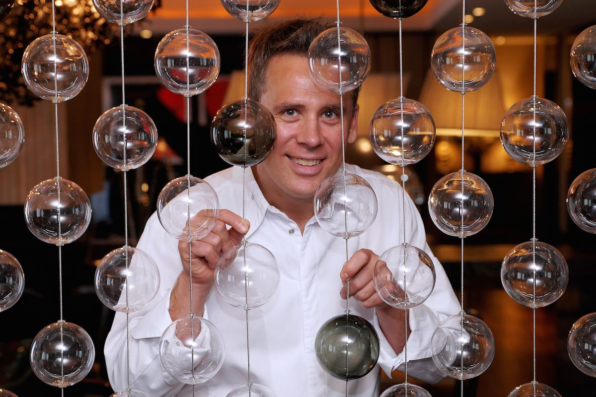 a man stands behind a curtain of glass bulbs