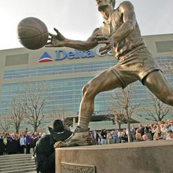 Karl Malone kisses the statue foot of former teammate John Stockton as he greets fans outside what was then the Delta Center on Thursday March 23, 2006