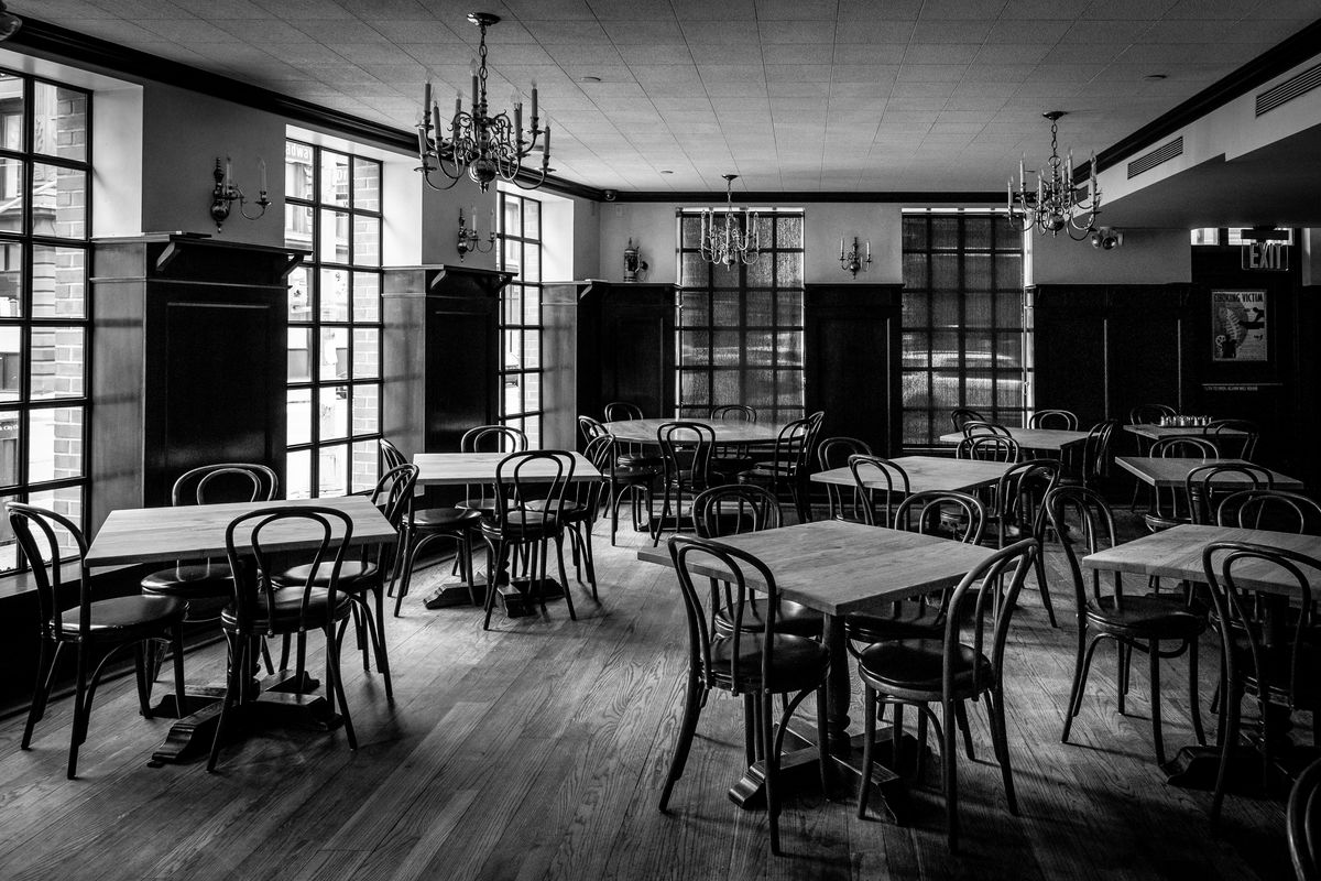 A black and white photo of an empty restaurant, with several tables-of-four