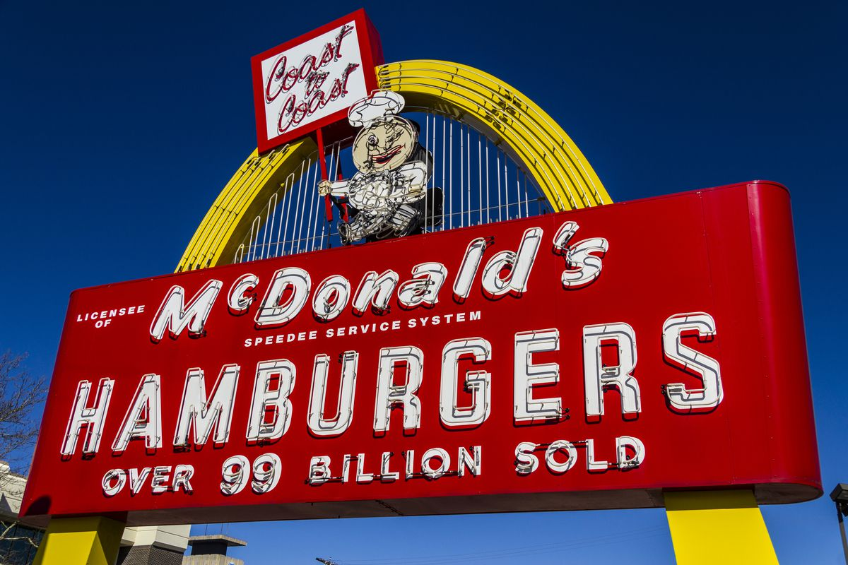 """Against a blue sky, a retro-inspired McDonald's monument sign composed of a yellow arch and red sign-board advertising """"McDonald's Hamburgers: Over 99 Billion Sold"""" in a peppy white font, all topped by Speedy, the original McDonald's mascot."""