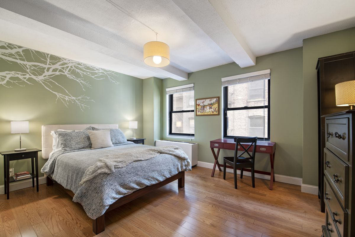 A bedroom with hardwood floors, light green walls, two windows, and beamed ceilings.
