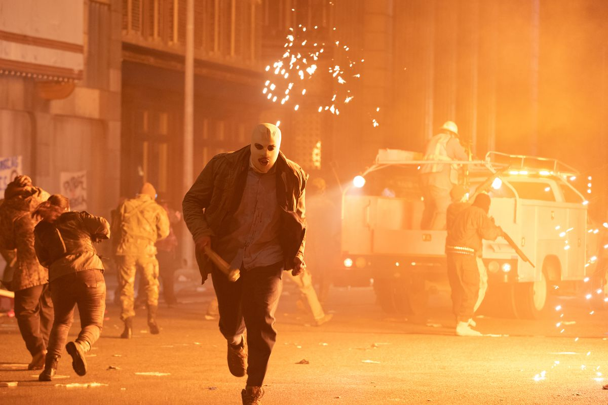 A masked purger runs from an explosion in The Forever Purge