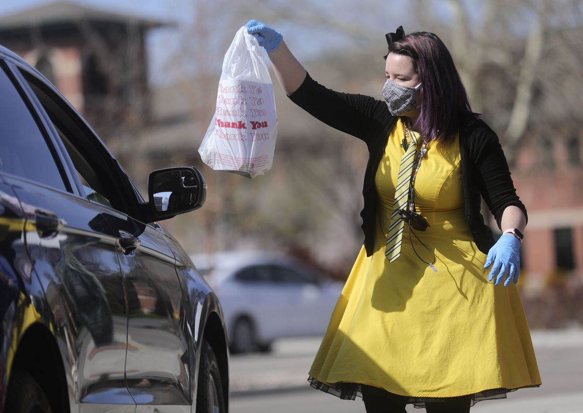 """Children's librarian Lauren Tolman, dressed as a Hufflepuff from """"Harry Potter,"""" delivers a bag of books to a customer outside of the Springville Library in Springville on Wednesday, April 8, 2020."""