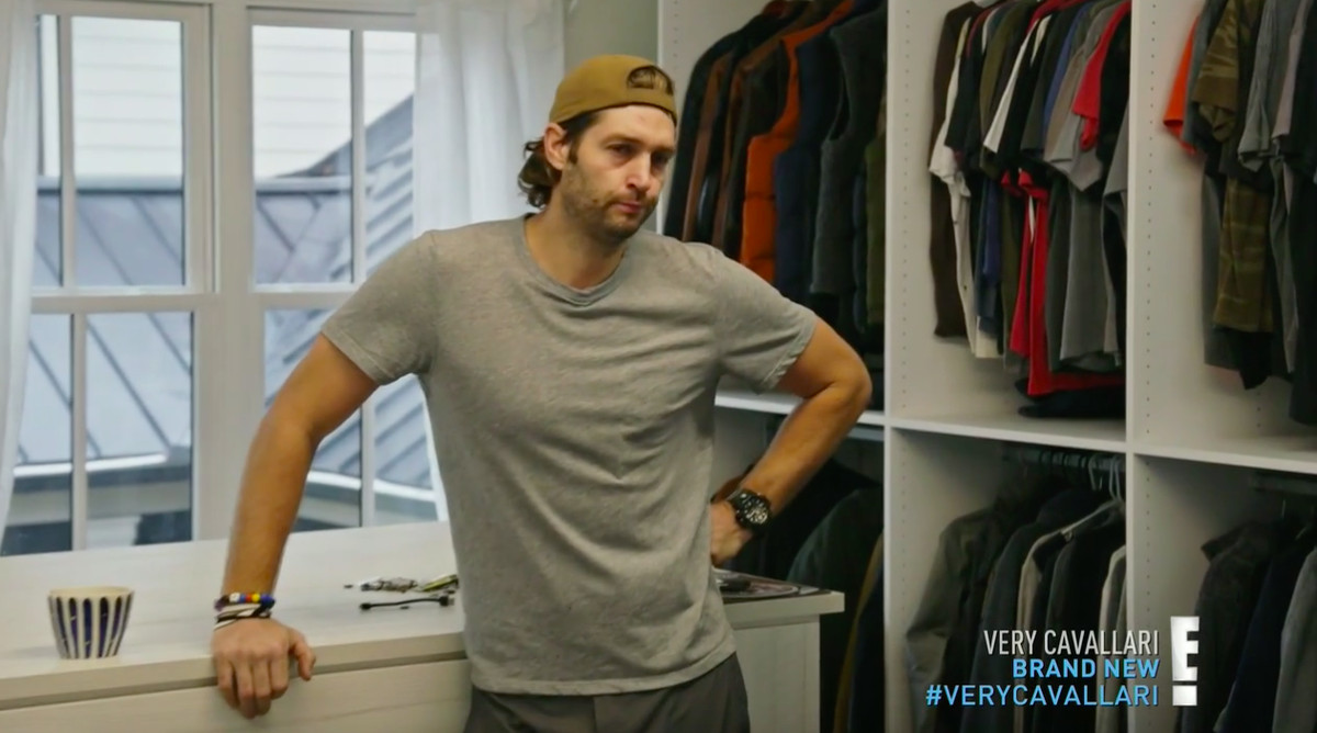 Jay Cutler standing with a hand on his hip next to his closet