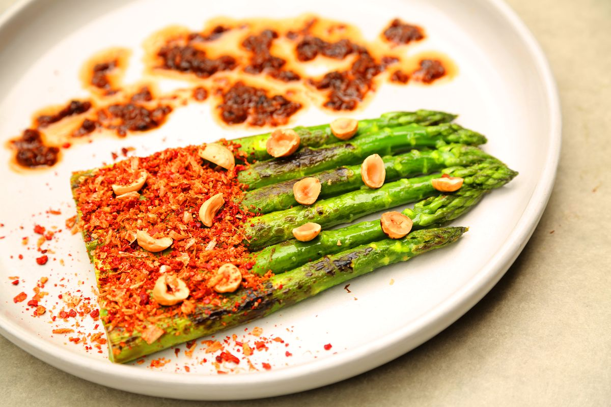 Five grilled asparagus are topped in hazelnut and a red xo sauce on a white plate