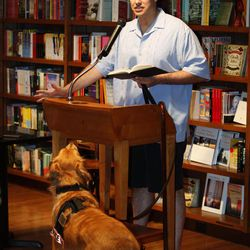 """In this June 28, 2011 photo, formerU.S. Army Capt. Luis Carlos Montalvan reads a passage from his book """"Until Tuesday,"""" as his service dog """"Tuesday"""" looks on during a book signing at a book store in Coral Gables, Fla. Since serving two tours of duty, for which he received two Bronze Stars and the Purple Heart, the former Army captain has become a strong critic of the war and an advocate for better care of those who served."""