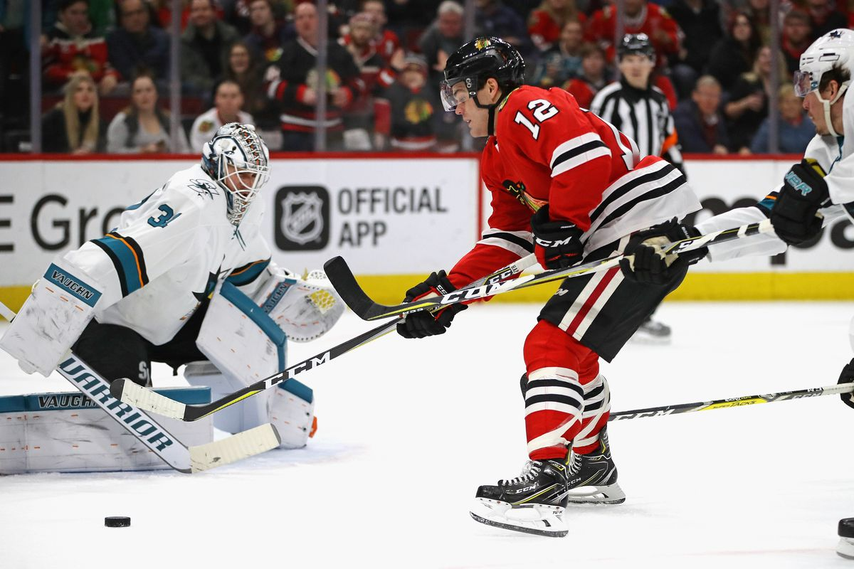 CHICAGO, IL - FEBRUARY 23: Alex DeBrincat #12 of the Chicago Blackhawks tries to get off a shot at Martin Jones #31 of the San Jose Sharks pressured by Justin Braun #61 at the United Center on February 23, 2018 in Chicago, Illinois. The Blackhawks defeate