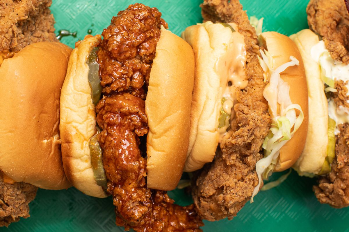Four habanero-brined fried chicken sandos turn on their sides upon a turquoise background from ghost kitchen Fuku, back by chef David Chang