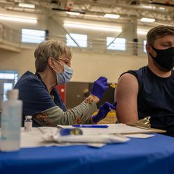 Marilyn Gertsch, left, gives Tanner Bingham, right, a COVID-19 vaccination at the Canyons School District's final COVID-19 vaccination clinic at Mount Jordan Middle School in Sandy on Thursday, March 11, 2021.