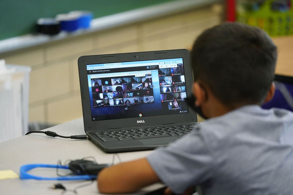 Boy participates in a video lesson on his laptop in a learning center.
