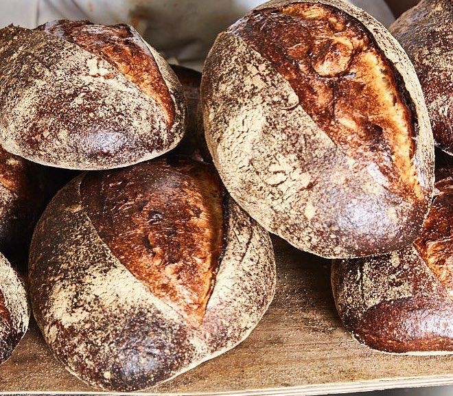 Whole loaves of dark brown sourdough bread rest on top of one another in a window display